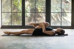 Giovane donna attraente in ginocchia alla posa del petto, fondo dello studio Fotografia Stock Libera da Diritti