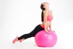 Giovane donna attraente messa a fuoco di forma fisica che fa allungamento sul fitball rosa Fotografie Stock