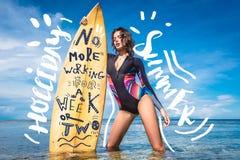 giovane donna attraente in muta umida con il surf che posa nell'oceano alla spiaggia Bali Indonesia del DUA di Nusa illustrazione di stock
