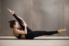 Giovane donna attraente nella posa alterna di allungamento della gamba, studi grigio Fotografia Stock