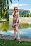 Giovane donna attraente Occhiali da sole rossi, vestito da colore Ritratto del ` s della ragazza Fondo dello stadio di football a fotografia stock libera da diritti
