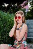 Giovane donna attraente Occhiali da sole rossi, vestito da colore Ritratto della giovane donna immagini stock