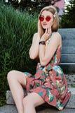 Giovane donna attraente Occhiali da sole rossi, vestito da colore Ritratto della giovane donna immagine stock libera da diritti