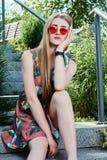 Giovane donna attraente Occhiali da sole rossi, vestito da colore Ritratto della giovane donna fotografie stock