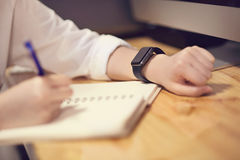 Giovane donna attraente in orologio astuto del frome della nota dell'ufficio sullo scrittorio Immagini Stock