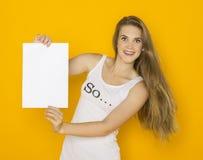 Giovane donna attraente piacevole che tiene carta in bianco Fotografia Stock