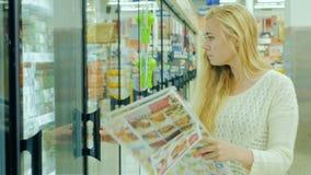 Giovane donna attraente sconti leggenti di una pubblicità a mezzo stampa Poi prende l'alimento dal frigorifero in video d archivio