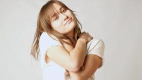 Giovane donna attraente sicura vaga nell'amore con se stessa che si abbraccia archivi video