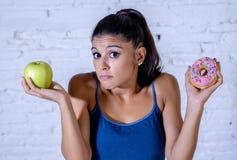 Giovane donna attraente su una dieta che decide fra una mela e una ciambella immagini stock libere da diritti