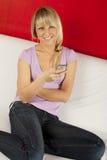 Giovane donna attraente sullo strato con il telefono Fotografia Stock