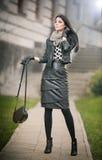 Giovane donna attraente in un colpo di modo di inverno. Bella ragazza alla moda in attrezzatura di cuoio nera che posa sul viale Fotografia Stock
