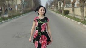 Giovane donna attraente in un vestito con i fiori che corre sulla strada principale archivi video