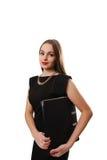 Giovane donna attraente in un vestito nero che sorride e che esamina c Immagine Stock