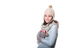 Giovane donna attraente in una maglietta grigia che tiene un vetro della bevanda Isolato su priorità bassa bianca immagini stock