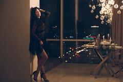 Giovane donna attraente in vestito da cocktail nero che si appoggia parete nella camera di albergo immagini stock