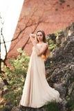 Giovane donna attraente in vestito lungo che sta sulle rocce Immagine Stock