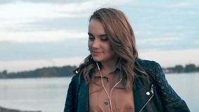 Giovane donna attraente vicino al fiume che ascolta la musica in cuffia archivi video
