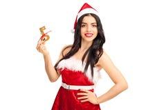 Giovane donna in attrezzatura di Santa che tiene una chiave Fotografia Stock Libera da Diritti