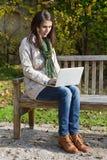 Giovane donna in autunno che si siede su una scrittura del banco di parco qualcosa Immagini Stock
