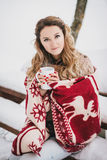 Giovane donna avvolta in coperta che beve tè caldo in foresta nevosa Immagine Stock Libera da Diritti