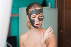 Giovane donna bianca che indossa una maschera di protezione a casa su un fondo del turchese Donna europea nella maschera nera per fotografie stock libere da diritti
