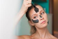 Giovane donna bianca che indossa una maschera di protezione a casa su un fondo del turchese Donna europea nella maschera nera per fotografia stock