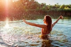 Giovane donna in bikini che gioca in acqua e che fa spruzzata Vacanza di estate immagini stock libere da diritti