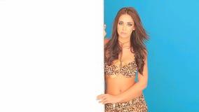 Giovane donna in bikini che tiene un cartello in bianco stock footage