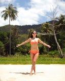 Giovane donna in bikini rosso che sta sulla spiaggia di sabbia fine, armi immagini stock libere da diritti