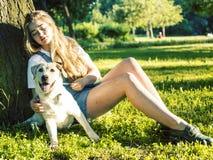 Giovane donna bionda attraente che gioca con il suo cane in parco verde all'estate, concetto della gente di stile di vita fotografia stock