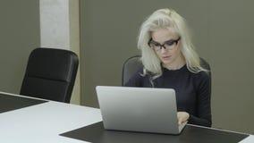 Giovane donna bionda attraente che lavora nell'ufficio sul computer portatile archivi video