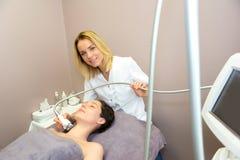 Giovane donna bionda attraente dell'estetista che fa un massaggio facciale t Fotografie Stock