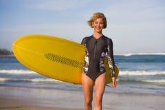 Giovane donna bionda attraente e felice del surfista in bella spiaggia che porta il bordo di spuma giallo che cammina dal mare ch fotografia stock libera da diritti