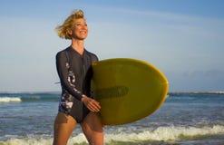 Giovane donna bionda attraente e felice del surfista in bella spiaggia che porta il bordo di spuma giallo che cammina dal mare ch immagini stock