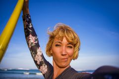 Giovane donna bionda attraente e felice del surfista nel bordo di spuma della tenuta del costume da bagno nella spiaggia che pren immagini stock libere da diritti