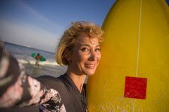 Giovane donna bionda attraente e felice del surfista nel bordo di spuma della tenuta del costume da bagno nella spiaggia che pren fotografia stock