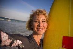 Giovane donna bionda attraente e felice del surfista nel bordo di spuma della tenuta del costume da bagno nella spiaggia che pren immagine stock