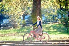 Giovane donna bionda attraente in vetri con la bicicletta di signora rosa sulla via della citt? il giorno di estate soleggiato fotografie stock
