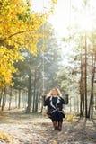 Giovane donna bionda caucasica in cardigan marrone che guida un'oscillazione nell'orientamento verticale della foresta gialla di  immagini stock libere da diritti