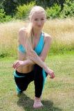 Giovane donna bionda che allunga le sue gambe sull'erba nel parco Fotografia Stock Libera da Diritti