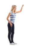 Giovane donna bionda che batte su una porta immagini stock