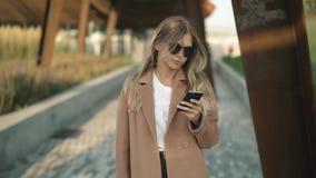Giovane donna bionda che cammina nel parco, esaminante smartphone, poi sorridente stock footage