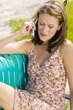 Giovane donna bionda che comunica sul suo telefono delle cellule fotografia stock