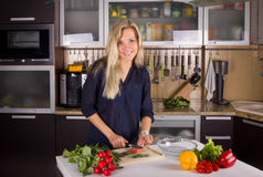 Giovane donna bionda che cucina insalata in cucina Immagine Stock Libera da Diritti
