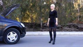 Giovane donna bionda che fa auto-stop sulla strada vicino all'automobile archivi video