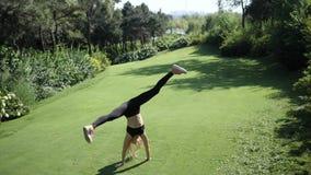 Giovane donna bionda che fa cartwheel sull'erba al rallentatore stock footage