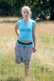 Giovane donna bionda che fa un allungamento del quadrato per le gambe nel parco Fotografie Stock