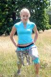 Giovane donna bionda che fa un allungamento della gamba per le gambe nel parco Fotografia Stock Libera da Diritti