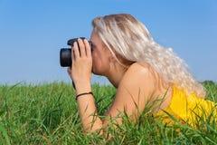 Giovane donna bionda che fotografa nell'erba fotografia stock libera da diritti