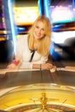 Giovane donna bionda che gioca roulette in casinò e nella conquista Fotografie Stock